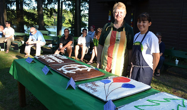 Lois and baker, Marcella, stand with their beautifully decorated Camp Highlands birthday cakes